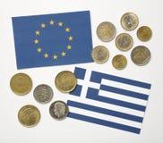 Bandera griega y bandera europea con las monedas de los euros y del dracma Imagenes de archivo