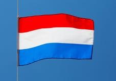 Bandera holandesa contra el cielo azul Foto de archivo