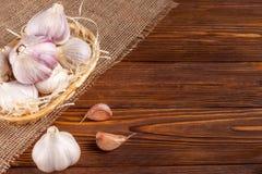 Bandera horizontal del ajo Eco que cultiva concepto Ajos y clavos enteros en cesta de la paja en el pedazo de despido en textur d Fotos de archivo libres de regalías