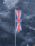 Bandera inglesa que agita contra el bosque cubierto por la nieve Foto de archivo libre de regalías