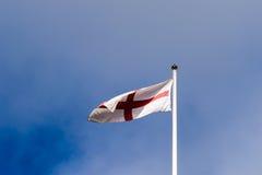 Bandera inglesa que agita contra el cielo azul nublado Foto de archivo libre de regalías