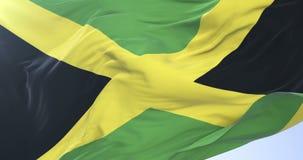 Bandera jamaicana que agita en el viento con el cielo azul en lento, lazo stock de ilustración
