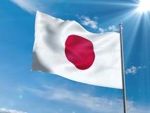 Bandera japonesa que agita en cielo azul con el sol Imagen de archivo