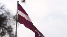 Bandera letona que agita en el alto del viento para arriba en el cielo durante una puesta del sol de oro de la hora - capital de  almacen de video