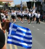 Bandera nacional de Grecia delante de la gente que marcha fotografía de archivo libre de regalías
