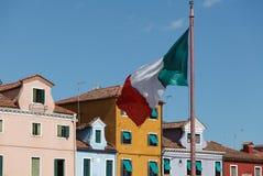 Bandera nacional de la mosca de Italia sobre cuadrado principal de la plaza de la isla de Burano Isla con las casas pintadas colo fotos de archivo libres de regalías