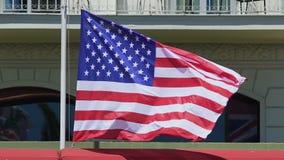 Bandera nacional del vuelo de los Estados Unidos de América en viento, subiendo sobre embajada metrajes
