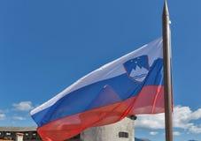 Bandera nacional eslovena sobre castillo sangrado Imagen de archivo