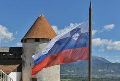 Bandera nacional eslovena sobre castillo sangrado Foto de archivo