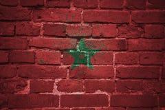Bandera nacional pintada de Marruecos en una pared de ladrillo imagenes de archivo