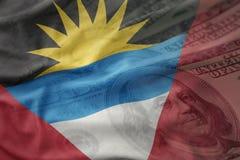 Bandera nacional que agita colorida de Antigua y de Barbuda en un fondo americano del dinero del dólar Fotos de archivo libres de regalías