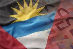 Bandera nacional que agita colorida de Antigua y de Barbuda en un fondo de los billetes de banco del dinero del euro Foto de archivo libre de regalías