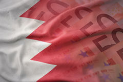 Bandera nacional que agita colorida de Bahrein en un fondo de los billetes de banco del dinero del euro foto de archivo