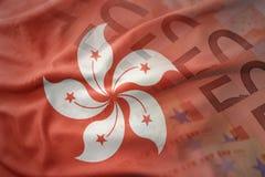 Bandera nacional que agita colorida de Hong-Kong en un fondo de los billetes de banco del dinero del euro Imagen de archivo