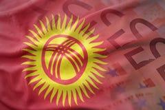 Bandera nacional que agita colorida de Kirguistán en un fondo de los billetes de banco del dinero del euro fotografía de archivo