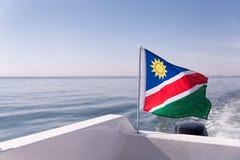 Bandera namibiana que sopla en el viento del océano Imágenes de archivo libres de regalías