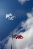 Bandera noruega en cielo Imágenes de archivo libres de regalías