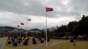 Bandera noruega que agita en el aire del cementerio conmemorativo de la O.N.U en Busán, Corea del Sur, Asia almacen de metraje de vídeo