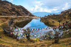Bandera o pulmón tibetana TA del rezo y al lado de la charca, la caída de la bandera encendido Fotos de archivo libres de regalías