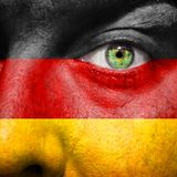 Bandera pintada en cara con el ojo verde para mostrar la ayuda de Alemania Foto de archivo