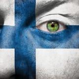 Bandera pintada en cara con el ojo verde para mostrar la ayuda de Finlandia Fotos de archivo libres de regalías