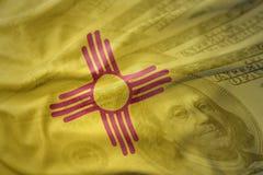 Bandera que agita colorida del estado de New México en un fondo americano del dinero del dólar imagen de archivo libre de regalías