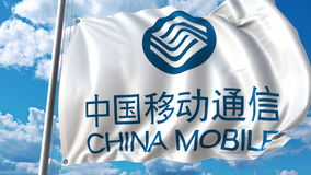 Bandera que agita con el logotipo de China Mobile contra el cielo y las nubes Representación editorial 3D Imagen de archivo