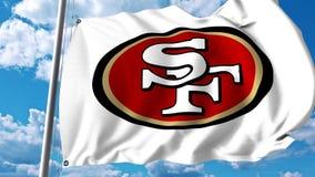 Bandera que agita con el logotipo profesional del equipo de los San Francisco 49ers Representación editorial 3D Foto de archivo