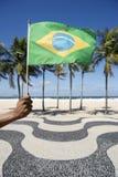 Bandera que agita Copacabana Rio Brazil de la mano brasileña Foto de archivo libre de regalías