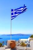 Bandera que agita de Grecia en la terraza en Santorini, potes de flores y vistas del mar del top Imagen de archivo
