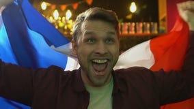 Bandera que agita del fan extremadamente feliz de Francia que disfruta la victoria nacional del equipo de deportes almacen de video