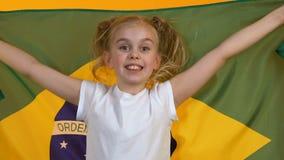 Bandera que agita del pequeño niño de la fan del Brasil, animando para el equipo de deportes nacional, ayuda metrajes