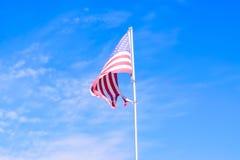 Bandera rasgada de los E.E.U.U. con el cielo azul imagen de archivo libre de regalías