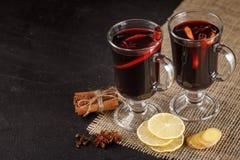 Bandera reflexionada sobre del vino Vidrios con el vino rojo y las especias calientes en fondo oscuro Estilo oscuro moderno del h Imagenes de archivo
