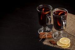 Bandera reflexionada sobre del vino Vidrios con el vino rojo y las especias calientes en fondo oscuro Estilo oscuro moderno del h Foto de archivo libre de regalías