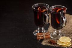 Bandera reflexionada sobre del vino Vidrios con el vino rojo y las especias calientes en fondo oscuro Estilo oscuro moderno del h Imágenes de archivo libres de regalías