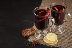 Bandera reflexionada sobre del vino Vidrios con el vino rojo y las especias calientes en fondo oscuro Estilo oscuro moderno del h Imagen de archivo libre de regalías