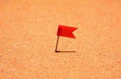 Bandera roja del post-it fijada en tablero del corcho Foto de archivo libre de regalías