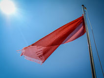 Bandera roja en la playa Fotografía de archivo