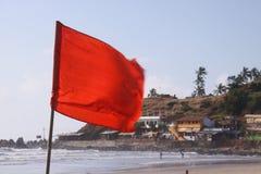 Bandera roja en la playa Fotografía de archivo libre de regalías