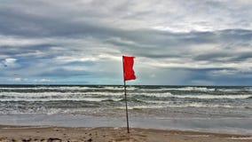 Bandera roja en la playa imagen de archivo libre de regalías