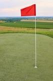 Bandera roja en terreno del golf Foto de archivo