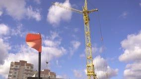 Bandera roja en un emplazamiento de la obra contra la perspectiva de la construcción de una casa de estancia y de una grúa, conce metrajes