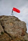 Bandera roja encima de una montaña Fotos de archivo libres de regalías