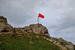 Bandera roja encima de una montaña contra Imagenes de archivo