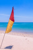 Bandera roja y amarilla en la playa imagen de archivo