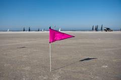 Bandera rosada en la playa con los barcos en fondo Imagen de archivo libre de regalías