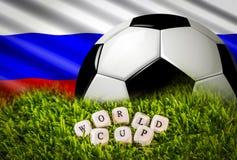 Bandera rusa, bola del fútbol en hierba verde y palabras del mundial Foto de archivo