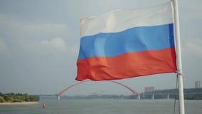 Bandera rusa que sopla con el puente bugrinskiy en el fondo del mar en el viaje de Novosibirsk en día nublado en lento almacen de metraje de vídeo