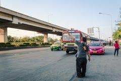 Bandera tailandesa del hombre abajo de un autobús Imagen de archivo libre de regalías